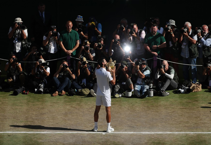 Novak Djokovic of Serbia kisses the trophy after defeating Kevin Anderson of South Africa in the men's singles final match at the Wimbledon Tennis Championships in London, Sunday July 15, 2018. (Daniel Leal-Olivas/Pool via AP)