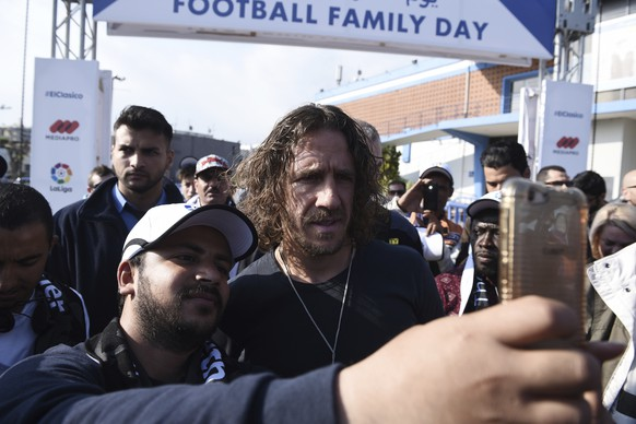 """A migrant takes a selfie with retired Spanish soccer player Carles Puyol at the Greek northern city of Thessaloniki, on Sunday, April 23, 2017. About 1000 refugees residing in northern Greece attended an event in the framework of """"Football Family Day"""" during which they watched a live broadcasting of a soccer match between Barcelona and Real Madrid on two giant screens. (AP Photo/Giannis Papanikos)"""