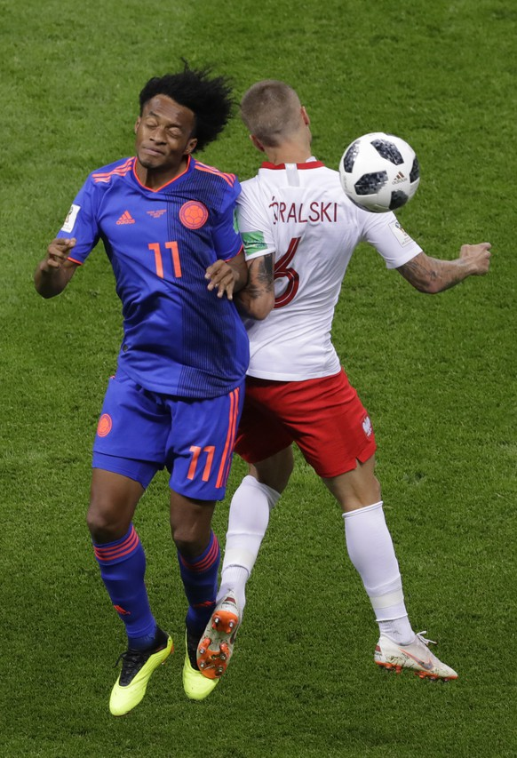 Colombia's Juan Cuadrado, left, and Poland's Jacek Goralski battle for the ball during the group H match between Poland and Colombia at the 2018 soccer World Cup at the Kazan Arena in Kazan, Russia, Sunday, June 24, 2018. (AP Photo/Sergei Grits)