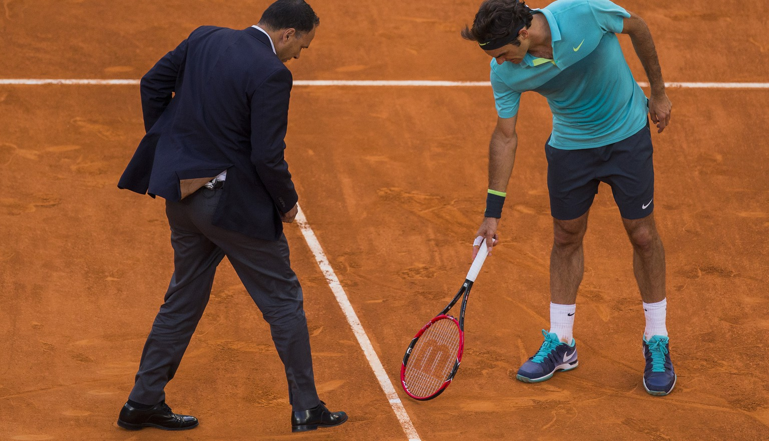 Roger Federer from Switzerland, right, talks to the umpire during the Madrid Open tennis tournament match against Nick Kyrgios from Australia in Madrid, Spain, Wednesday, May 6, 2015. (AP Photo/Andres Kudacki)