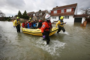 WRAYSBURY, ENGLAND - FEBRUARY 11:  Members of Royal Berkshire Fire & Rescue squad evacuate a family from flooded Wraysbury on February 11, 2014 in Wraysbury, England. The Environment Agency has issued severe flood warnings for a number of areas on the river Thames west of London.  (Photo by Peter Macdiarmid/Getty Images)