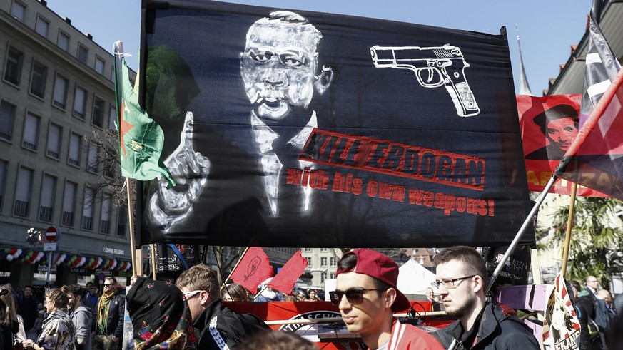 epa05870523 A banner reads; 'Kill Erdogan with his own weapons', as protesters march during a demonstration against the Turkish President Recep Tayyip Erdogan, in Bern, Switzerland, 25 March 2017.  EPA/PETER KLAUNZER