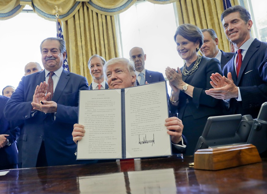 President Donald Trump holds up an executive order after signing it in the Oval Office of the White House in Washington, Friday, Feb. 24, 2017. Dow Chemical President, Chairman and CEO Andrew Liveris is at left. The executive order would establish regulatory reform officers and task forces within federal agencies a part of his push to slash federal government regulations. (AP Photo/Pablo Martinez Monsivais)