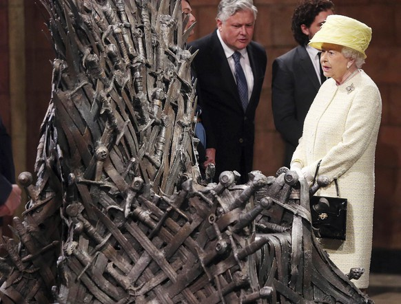 Britain's Queen Elizabeth looks at the Iron Throne next to Game of Thrones cast members Kit Harington (2nd R), Conleth Hill (C) and Lena Headey (L), on the set of the television series in the Titanic Quarter of Belfast, Northern Ireland, June 24, 2014. REUTERS/Jonathan Porter/Pool (NORTHERN IRELAND - Tags: ROYALS ENTERTAINMENT SOCIETY)