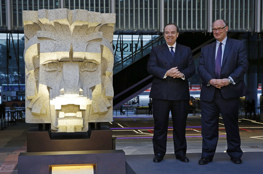 HSBC Group Chief Executive Stuart Gulliver, left, and Chairman Douglas Flint pose for a photo beside one of the pair of granite lion's head sculptures during the opening ceremony of the