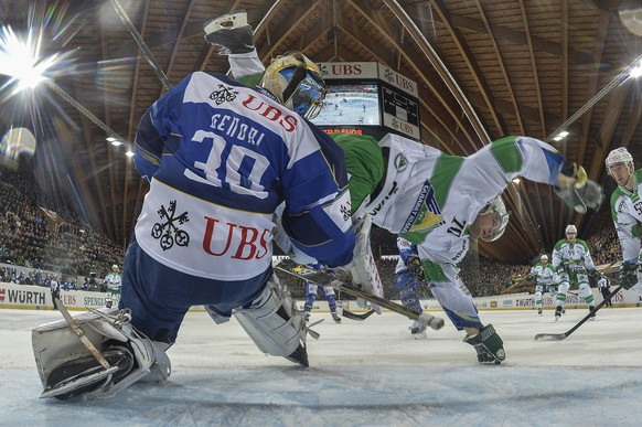 Davos' goalkeeper Leonardo Genoni, left, fights for the puck against Ufa's Teemu Hartikainen during the game between Switzerland's HC Davos and Russia's HC Salavat Yulaev Ufa in the semi final game at the 88th Spengler Cup ice hockey tournament in Davos, Switzerland, Tuesday, December 30, 2014. (KEYSTONE/Peter Schneider)