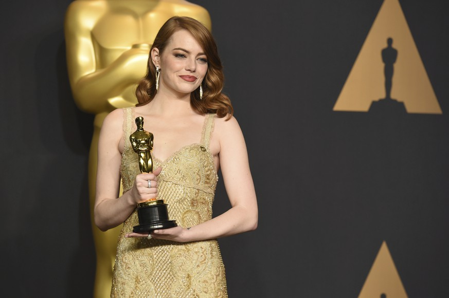 Emma Stone poses in the press room with the award for best actress in a leading role for