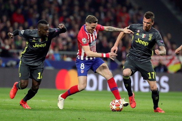epa07383885 Atletico de Madrid's midfielder Saul Niguez (C) vies for the ball against Juventus' midfielder Blaise Matuidi (L) and forward Mario Mandzukic (R) during the UEFA Champions League round of 16 first leg match between Atletico de Madrid and Juventus at Wanda Metropolitano stadium in Madrid, Spain, 20 February 2019.  EPA/JuanJo Martin