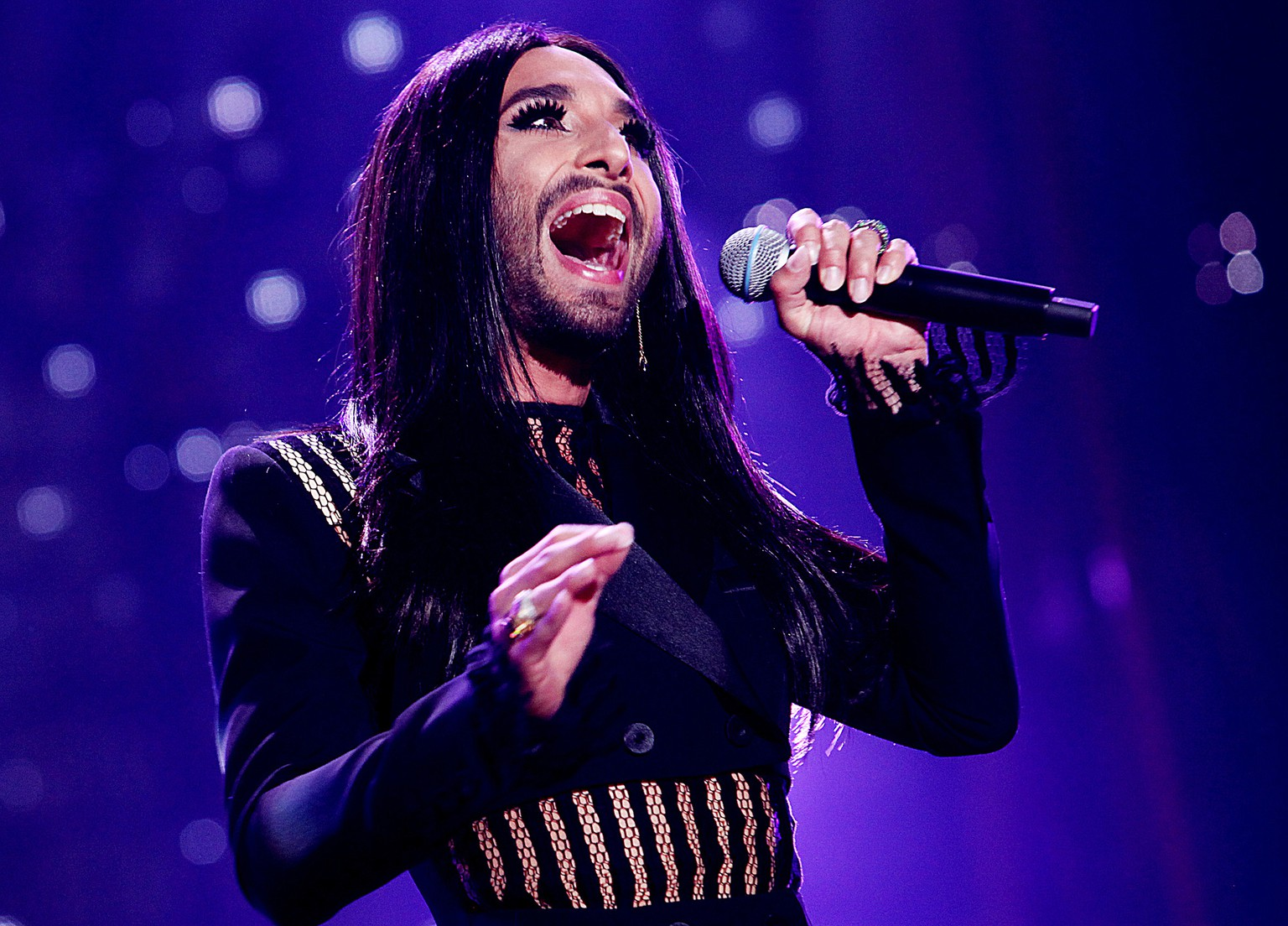 Austrian cross-dressing diva Conchita Wurst sings at a concert in Kielce, Poland, on Saturday, June 27, 2015. Local authorities banned music fans from bringing glass bottles and metal objects to the concert, as a precaution. Wurst's appearance at last year's Eurovision song contest shocked many in conservative Poland, but her talent earned her an invitation to Kielce.(AP Photo/Jarek Praszkiewicz) POLAND OUT