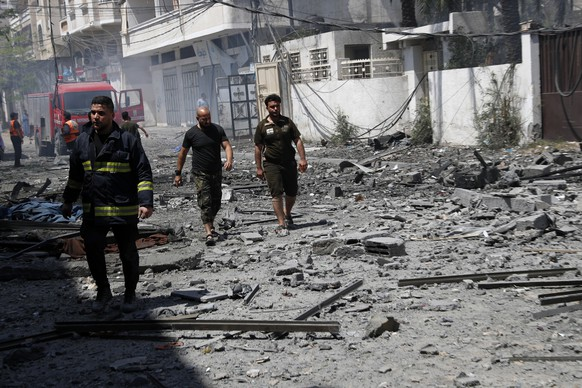 A firefighter and others inspect the rubble of a residential building that was hit by an Israeli airstrike, in Gaza City, Sunday, May 16, 2021. (AP Photo/Adel Hana)