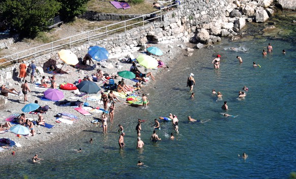 epa08518607 Foreign tourists bask in the sun at a beach in the town of Opatija, Croatia, 30 June 2020. Croatia has reopened its borders to visitors from abroad following months of closure due to the ongoing pandemic of the COVID-19 disease caused by the SARS-CoV-2 coronavirus. According to the country's tourism minister, Gari Cappelli, Croatia has so far welcomed 350,000 foreign tourists traveling from within the European Union.  EPA/ANTONIO BAT