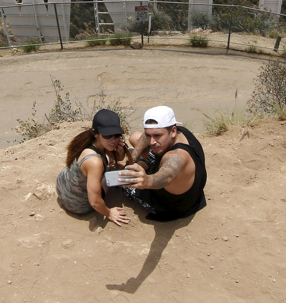 A couple poses for a selfie behind the Hollywood sign in Los Angeles, California, United States July 9, 2015. Hollywood Hills residents sued the city last week, according to local media. They demanded the closure of a popular Hollywood sign viewing path, until effects the crowds have on the neighborhood is assessed. REUTERS/Lucy Nicholson