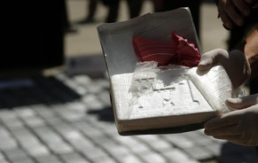 An officer from the National Gendarmerie (military border police) shows the content of a package of cocaine to be burnt at their headquarters in Buenos Aires March 10, 2014. A total of 230 kg were confiscated from an international drug smuggling gang in a recent police operation in the northern Argentine province of Corrientes, police authorities informed. REUTERS/Marcos Brindicci (ARGENTINA - Tags: DRUGS SOCIETY CRIME LAW)
