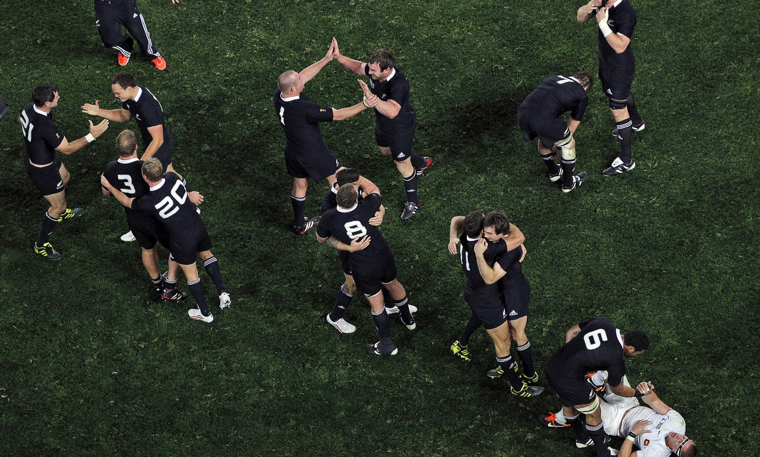 New Zealand All Blacks Jerome Kaino helps up France's Imanol Harinordoquy as his teammates celebrate after their Rugby World Cup final win over France at Eden Park in Auckland, New Zealand, Sunday, Oct. 23, 2011. (KEYSTONE/AP Photo/Natacha Pisarenko)