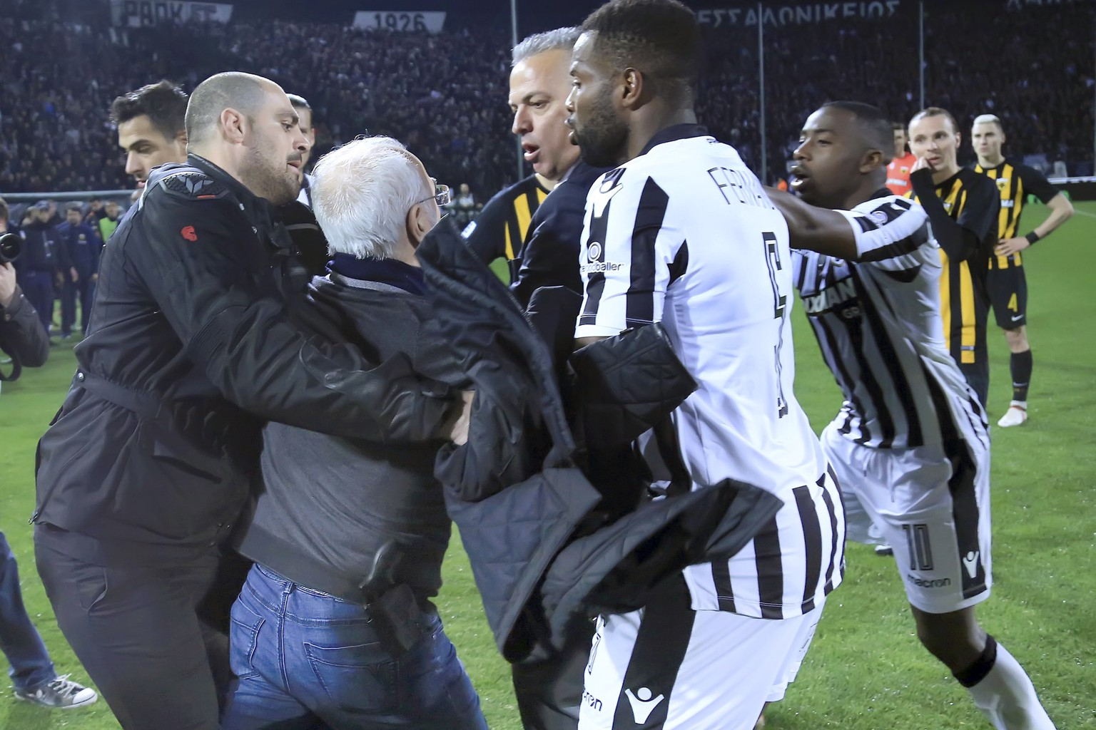 PAOK owner, businessman Ivan Savvidis, second from left, approaches AEK Athens' Manager Operation Department Vassilis Dimitriadis, center, as his bodyguard and PAOK's players Fernando Varela, second from right, and Djalma Campos, right, try to stop him during a Greek League soccer match between PAOK and AEK Athens in the northern Greek city of Thessaloniki, Sunday, March 11, 2018. A disputed goal at the end of the Greek league match led to a pitch invasion by Savvidis, who appeared to be carrying a gun. Savvidis came on the field twice. It's unclear this photos shows his first time or second. (InTime Sports via AP)