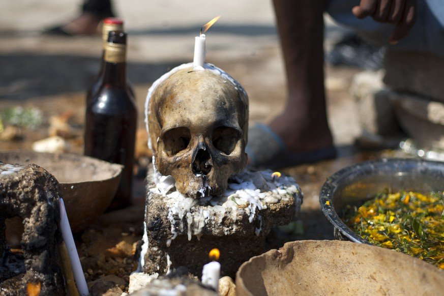 A human skull sits on a concrete block at the National cemetery during a Voodoo ritual that pays tribute to Baron Samdi and the Gede family of spirits during Day of the Dead celebrations in Port-au-Prince, Haiti, Sunday, Nov. 2, 2014. Day of the Dead traditions coincide with All Saints Day and All Souls Day on Nov. 1 and 2. (AP Photo/Dieu Nalio Chery)