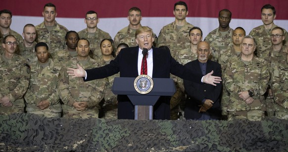 FILE - In this Nov. 28, 2019 file photo, President Donald Trump, center, with Afghan President Ashraf Ghani and Joint Chiefs Chairman Gen. Mark Milley, behind him at right, addresses members of the military during a surprise Thanksgiving Day visit at Bagram Air Field, Afghanistan. During his election campaign four years ago, Trump vowed to bring all troops home from