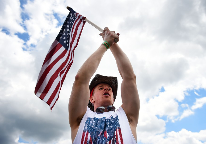 BALTIMORE, MD - MAY 17: A fan holds an American flag in the infield prior to the 139th running of the Preakness Stakes at Pimlico Race Course on May 17, 2014 in Baltimore, Maryland.   Patrick Smith/Getty Images/AFP == FOR NEWSPAPERS, INTERNET, TELCOS & TELEVISION USE ONLY ==