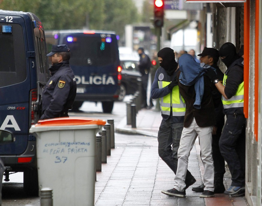 epa05008537 Police escort a man arrested in Madrid, Spain, accused of being related to the Islamic State on 03 November 2015. The Spanish Police has detained three people from Morocco accused of plotting terrorist attacks with a group linked to the Islamic State (IS).  EPA/VíICTOR LERENA