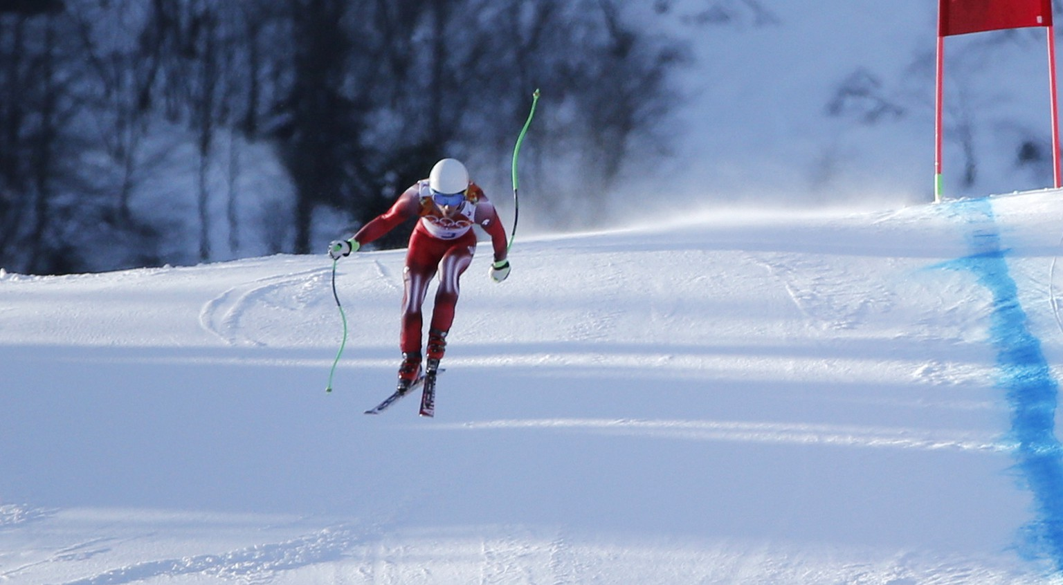 Switzerland's Carlo Janka makes the final jump during a men's downhill training run for the Sochi 2014 Winter Olympics, Friday, Feb. 7, 2014, in Krasnaya Polyana, Russia. (AP Photo/Christophe Ena)