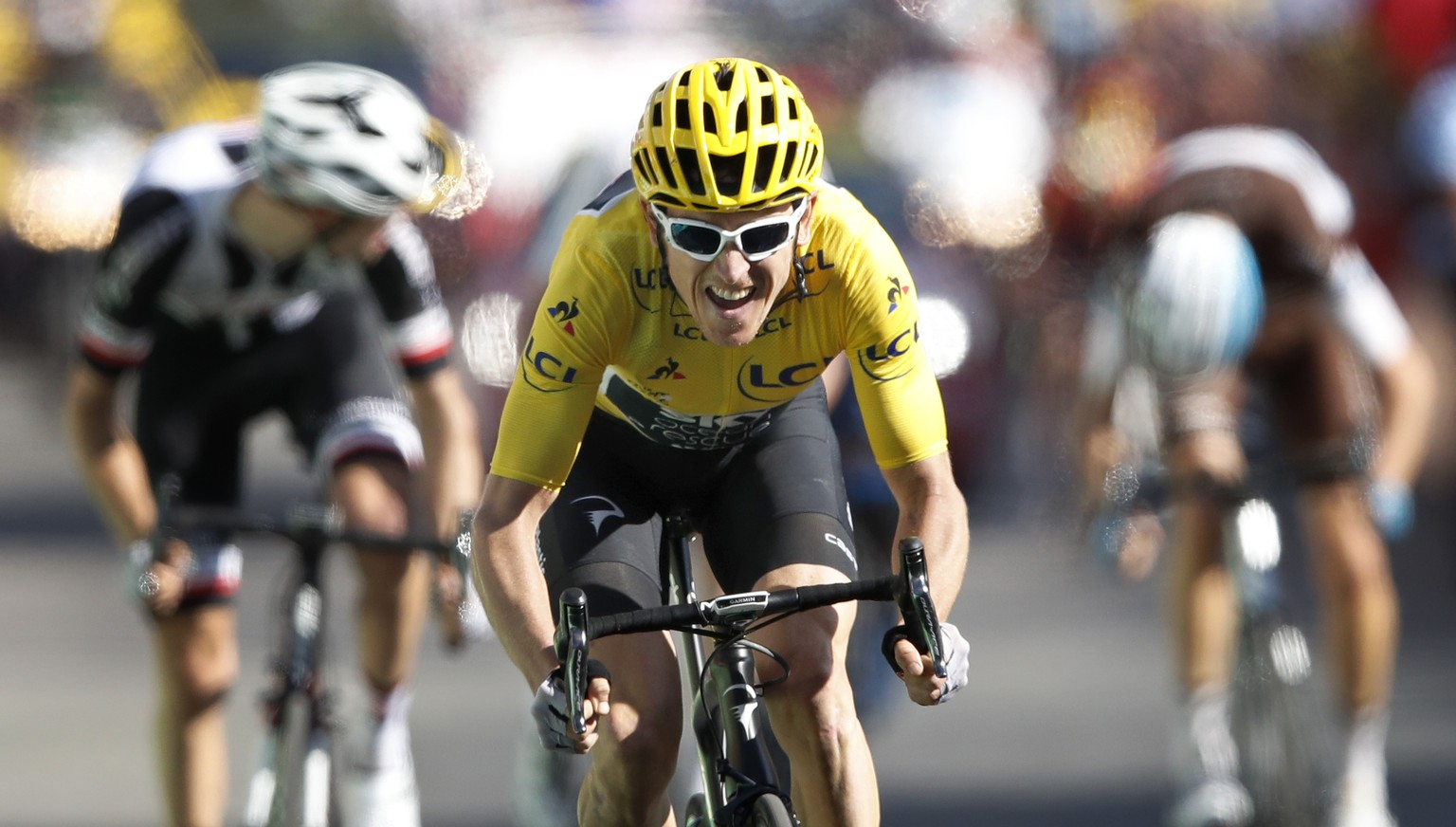Britain's Geraint Thomas, wearing the overall leader's yellow jersey speeds to the finish line to win the twelfth stage of the Tour de France cycling race over 175.5 kilometers (109 miles) with start in Bourg-Saint-Maurice Les Arcs and Alpe d'Huez, France, Thursday, July 19, 2018. (AP Photo/Christophe Ena )