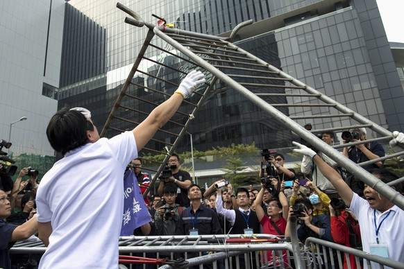 Building employees dismantle a barricade outside Citic Tower in accordance with a court injunction to clear up part of the protest site, outside the government headquarters in Hong Kong November 18, 2014. Hong Kong on Tuesday started to clear part of a protest camp in the heart of the city that has been occupied by pro-democracy demonstrators for nearly two months, leaving most of the main protest site intact. REUTERS/Tyrone Siu (CHINA - Tags: POLITICS CIVIL UNREST CRIME LAW) - RTR4EILV