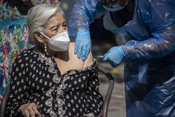 Alicia Martinez gets her second dose of China's Sinovac COVID-19 vaccine in the outdoor patio of a home for the elderly in Santiago, Chile, Friday, March 5, 2021. (AP Photo/Esteban Felix)