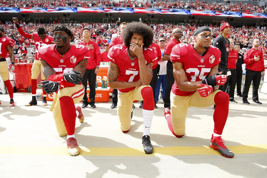 JAHRESRUECKBLICK 2016 - SPORT - epa05567442 San Francisco 49ers back-up quarterback Colin Kaepernick (C), San Francisco 49ers outside linebacker Eli Harold (L), and San Francisco 49ers free safety Eric Reid (R) take a knee during the US national anthem before the NFL game between the Dallas Cowboys and the San Francisco 49ers at Levi's Stadium in Santa Clara, California, USA, 02 October 2016. Kaepernick is protesting police brutality and oppression in America.  KEYSTONE/EPA/JOHN G MABANGLO
