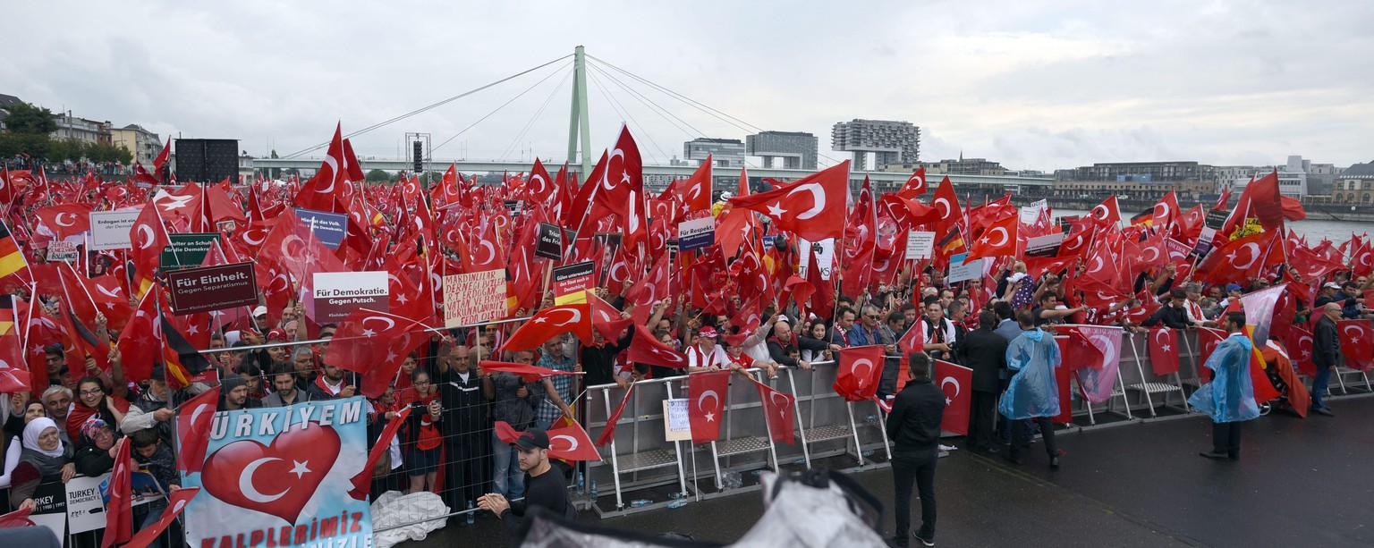 epa05449964 Supporters and protestors wave Turkish flags at the start of a pro-Erdogan rally in Cologne, Germany, 31 July 2016. Extra police have been deployed to Cologne where tens of thousands of protestors are expected to participate in the pro-Erdogen rally, in support of the Turkish President.  EPA/HENNING KAISER