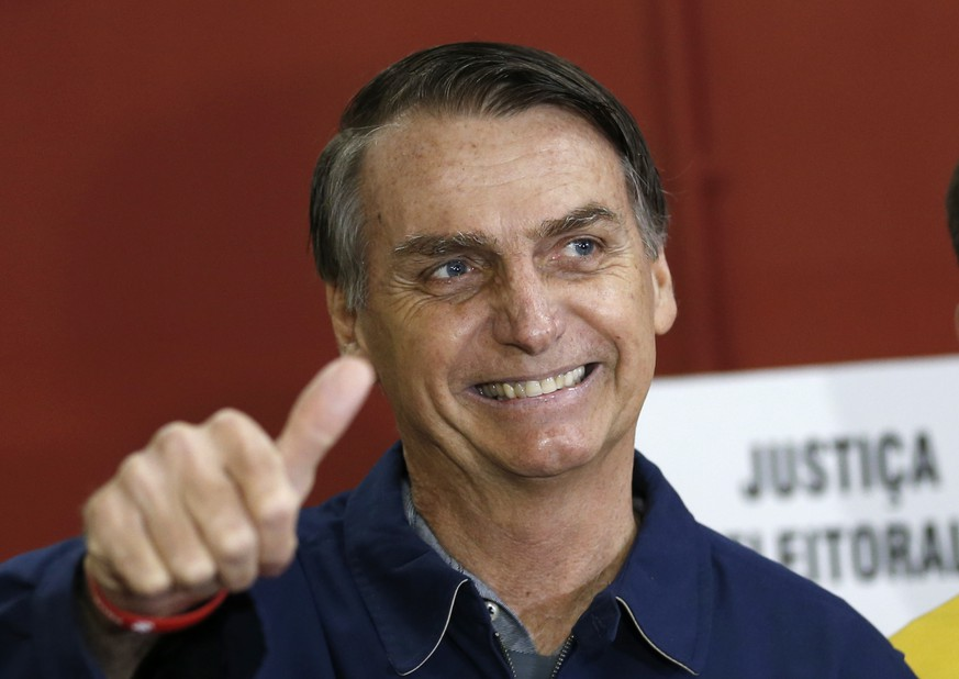 FILE - In this Oct. 7, 2018 file photo, presidential frontrunner Jair Bolsonaro, of the Social Liberal Party, flashes a thumbs up at a polling station in Rio de Janeiro, Brazil. In the first round of voting on Oct. 7, Bolsonaro performed far beyond expectations, nearly winning outright with 46 percent of the vote. (AP Photo/Silvia Izquierdo, File)
