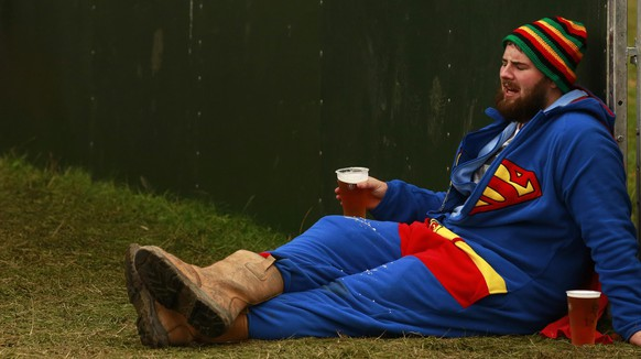 A festival goer in a Superman suit sits beside the main stage on the second day of the Electric Picnic music festival at Stradbally Hall in County Laois August 30, 2014. REUTERS/Cathal McNaughton (IRELAND - Tags: ENTERTAINMENT SOCIETY)