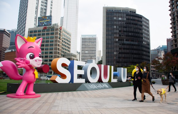 epaselect epa08736975 People wearing a masks walk outside Seoul City Hall in Seoul, South Korea, 12 October 2020. The South Korean government decided to lower its social distancing guidelines to the lowest level on 11 October amid a noticeable slowdown in new coronavirus cases.  EPA/JEON HEON-KYUN