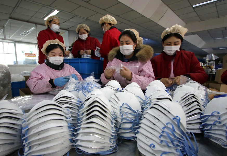 epaselect epa08153264 Workers manufacture protective face masks in a factory, as face mask stocks run low amid the outbreak of coronavirus, in Handan, Hebei Province, China, 23 January 2020. The outbreak of coronavirus has so far claimed 17 lives and infected more than 550 others, according to media reports. Authorities in Wuhan announced on 23 January, a complete travel ban on residents of Wuhan in an effort to contain the spread of the virus.  EPA/STRINGER CHINA OUT