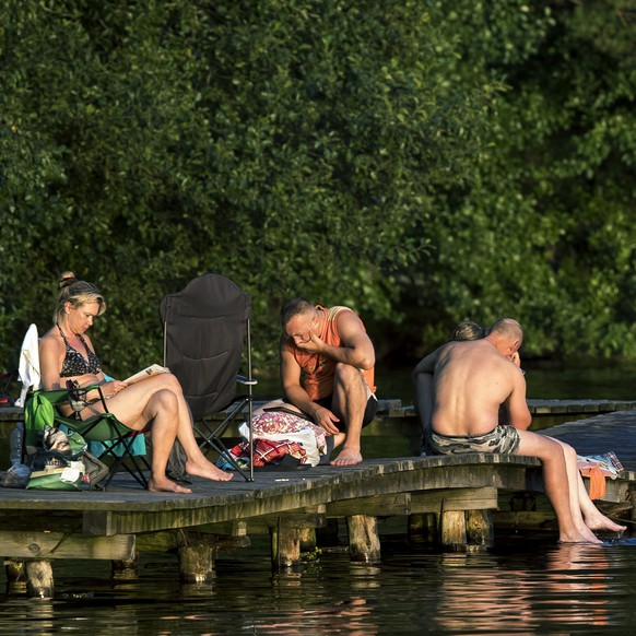 People sunbathe enjoying warm weather on a lake near Vilnius, Lithuania, Thursday, Aug. 2, 2018. Hot weather has set in with temperatures rising up to 32 Celsius (89,6 Fahrenheit) in Vilnius (AP Photo/Mindaugas Kulbis)