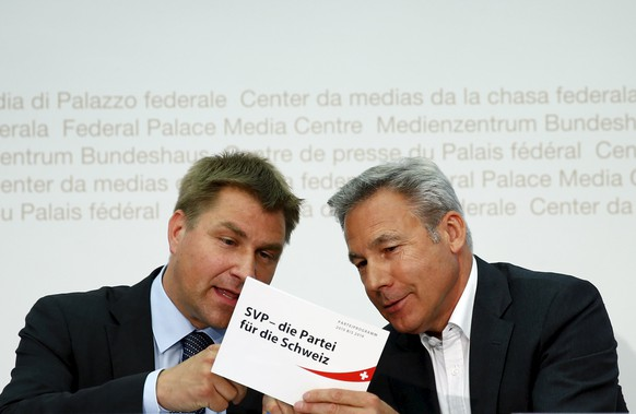 Swiss People's Party SVP President Toni Brunner (L) speaks with SVP faction President and National Councilor Adrian Amstutz before a news conference on the asylum politics in Bern, Switzerland May 26, 2015. The slogan on the paper reads: