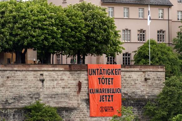 Ein Transparent, das zur Klimarebellion aufruft, haengt an der Mauer der Pfalz in Basel, am Freitag, 21. Mai 2021. (KEYSTONE/Georgios Kefalas)