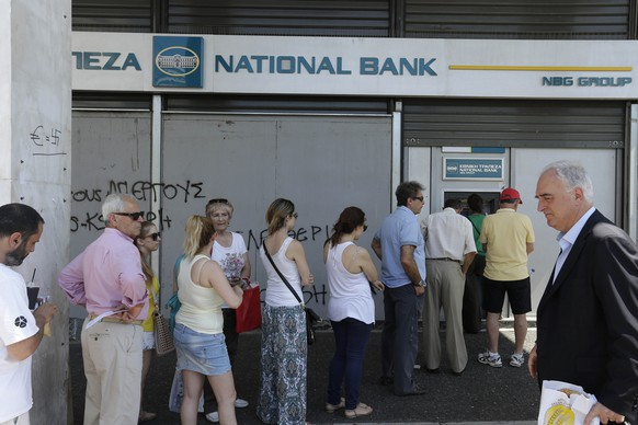 People line up to use ATM machines of a bank after government's decision for limited daily cash withdrawals to 60 euros ($67), in Athens, on Monday, July 6, 2015. Greek Finance Minister Yanis Varoufakis resigned Monday, saying he was told shortly after Greece's decisive referendum result that some other eurozone finance ministers and the country's other creditors would appreciate his not attending the ministers' meetings. (AP Photo/Thanassis Stavrakis)