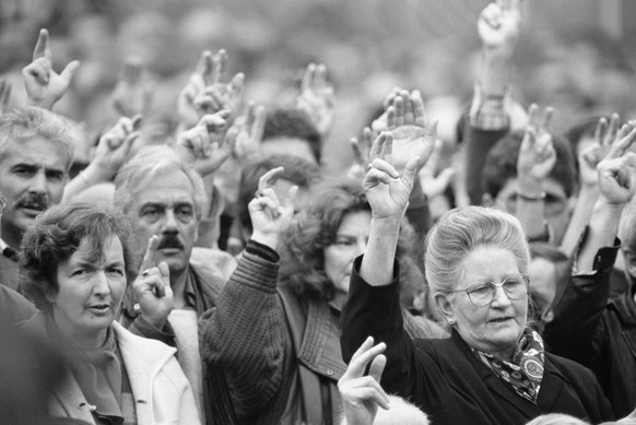 For the first time in history, men and women jointly raise their hands to vote at the