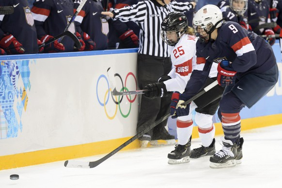 USAs defender Megan Bozek, right, fights for the puck against Switzerland's forward Alina Mueller, left, during a women's preliminary Group A game between Switzerland and the USA at the XXII Winter Olympics 2014 Sochi at the Shayba arena in Sochi, Russia, on Monday, February 10, 2014. (KEYSTONE/Laurent Gillieron)