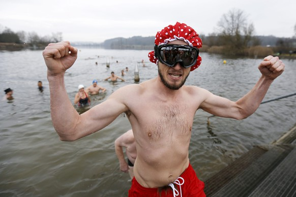 epa05084316 Brave swimmers get out of the four degree Celsius cold water of the Moossee lake at Moosseedorf, Switzerland, 31 December 2015, after their traditional New Year's Eve swim.  EPA/PETER KLAUNZER
