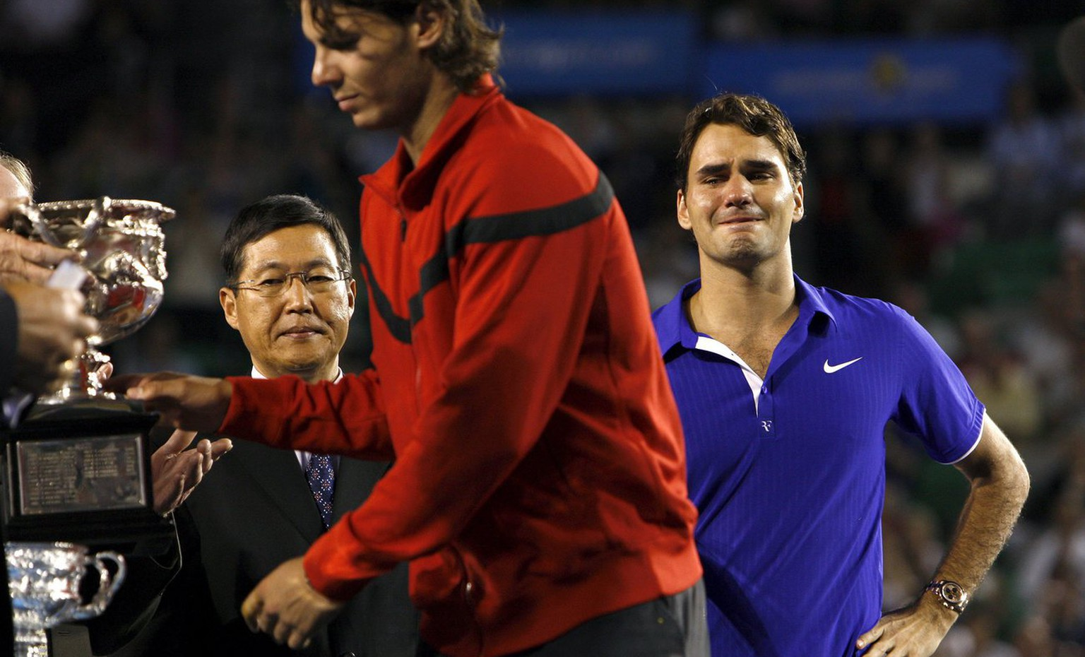 epa01621208 Swiss Roger Federer (R) looks at Spanish player Rafael Nadal receiving the winner's trophy after the men's final match at the Australian Open tennis tournament in Melbourne, 01 February 2009. Rafael Nadal won 7-5, 3-6, 7-6, 3-6, 6-2.  EPA/OLIVER WEIKEN