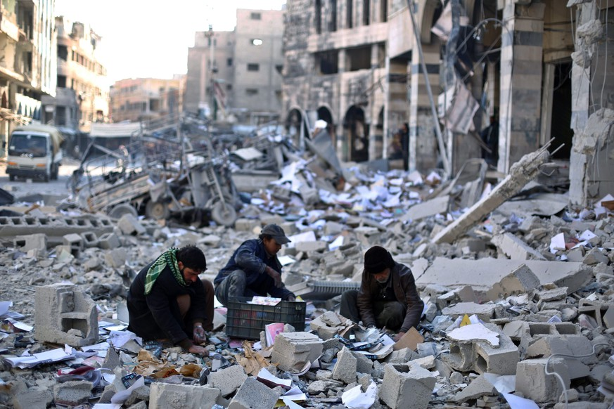 epaselect epa05083900 Syrians pick amongst the debris around the bombed out remains of a local council building hit in an airstrike carried out by forces allied with the al-Assad regime on opposition held Douma, outskirts of Damascus, Syria, 30 December 2015. Local reports have as yet not been able to identify the number of deaths and casualties in the latest airstrike on the town, which has been consistently bombed by the regime, leading to the deaths of hundreds of civilians and leaving thousands wounded.  EPA/MOHAMMED BADRA
