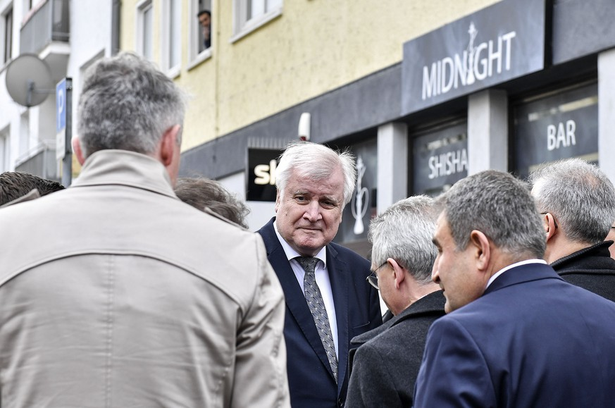 German Interior Minister Horst Seehofer stands in front of the hookah bar where several people were killed late Wednesday in Hanau, Germany, Thursday, Feb. 20, 2020. A 43-year-old German man shot and killed nine people at several locations in a Frankfurt suburb overnight in attacks that appear to have been motivated by far-right beliefs, officials said Thursday. (AP Photo/Martin Meissner)