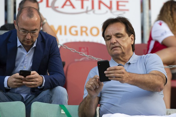 Alexandre Zen-Ruffinen, left, lawyer of FC Sion, and Christian Constantin, President of FC Sion, look on their smart phone, right, prior the Super League soccer match between FC Sion and BSC Young Boys, at the Stade de Tourbillon stadium, in Sion, Switzerland, Friday, July 31, 2020. All Super League soccer matches of Swiss Championship are played to behind the semi closed doors (only 1000 persons can be present in the stadium) due to preventive measure against a second wave of the coronavirus COVID-19. (KEYSTONE/Salvatore Di Nolfi)