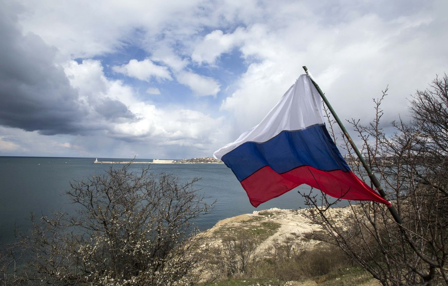 A Russian flag flies on the bank of the Black Sea during celebrations for the first anniversary of the Crimean treaty signing in Sevastopol, March 18, 2015. Russia's flag is flying across Crimea on the anniversary of what President Vladimir Putin calls the region's historic