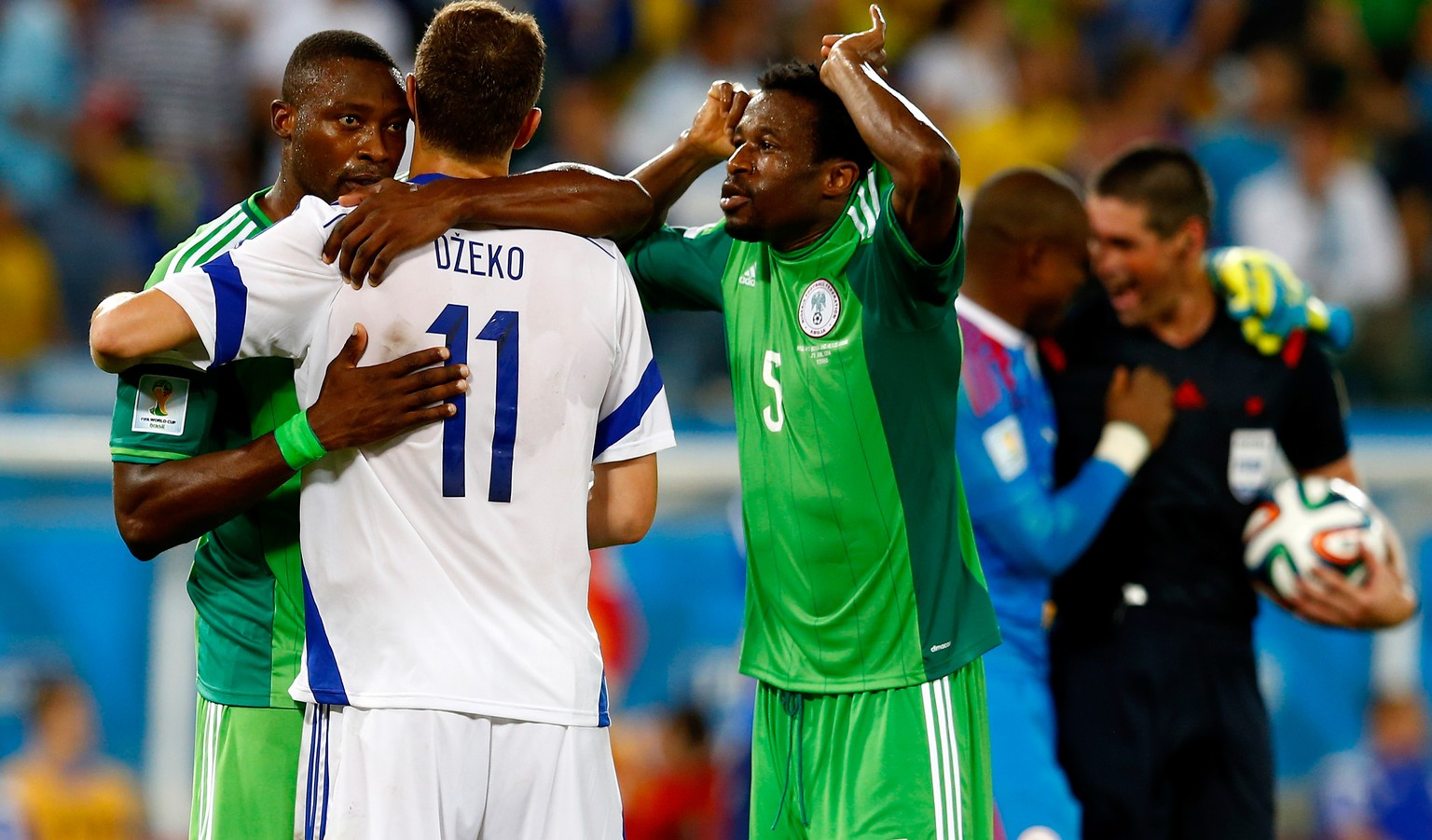 CUIABA, BRAZIL - JUNE 21:  Shola Ameobi of Nigeria hugs Edin Dzeko of Bosnia and Herzegovina after a 1-0 Nigeria win during the 2014 FIFA World Cup Group F match between Nigeria and Bosnia-Herzegovina at Arena Pantanal on June 21, 2014 in Cuiaba, Brazil.  (Photo by Matthew Lewis/Getty Images)