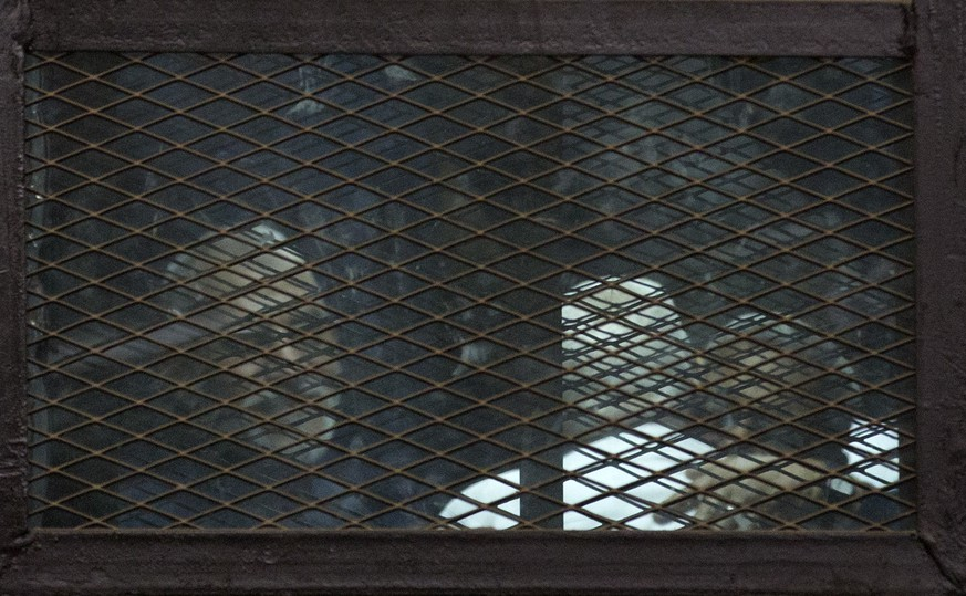 Muslim Brotherhood Supreme Guide Mohammed Badie, left, appears in a courtroom cage, in Cairo, Egypt, Saturday, Feb. 28, 2015. The Egyptian court sentenced four members of the banned Muslim Brotherhood organization to death and 14 to life in prison on Saturday. Badie and his deputy Khairat al-Shater were among those sentenced to life, along with former lawmaker Mohammed el-Beltagy and party head Saad el-Katatni and his deputy, Essam el-Erian. The men were accused of murder and possession of firearms, among other charges. The verdict can be appealed. (AP Photo/Hassan Ammar)