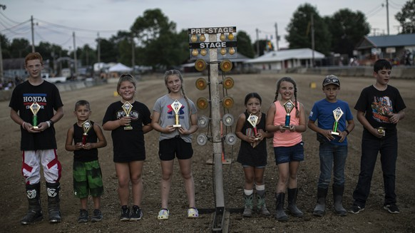 Young motorcycle and APV racers pose with their trophies at the Perry State Fair in New Lexington, Ohio, Friday, July 24, 2020. (AP Photo/Wong Maye-E)