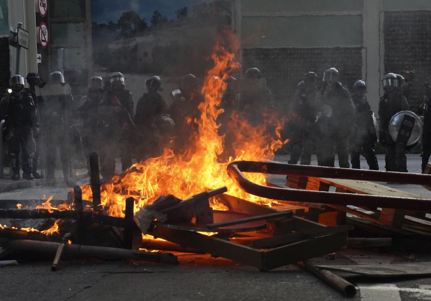 Police face a burning barricade during protests Saturday, Sept. 21, 2019, in Hong Kong. Demonstrators have marched through an outlying district of Hong Kong in another weekend of protest aimed at the Chinese territory's government. (AP Photo/Vincent Yu)