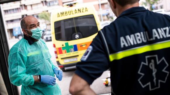 Mitarbeiter des Gruenen Kreuzes von Lugano desinfizieren einen Ambulanzwagen nach einem Einsatz, am Donnerstag, 5. Maerz 2020, in Lugano. Aufgrund des Coronavirus gelten hoechstmoegliche Hygienemassnahmen. (KEYSTONE/Ti-Press Pool)